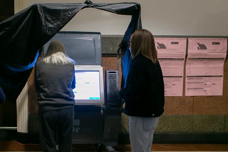 A voter learns to use new voting machines at Philadelphia City Hall before the 2019 general election.