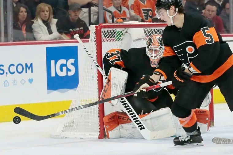 Flyers defenseman Phil Myers knocking down the puck as goalie Brian Elliott keeps a watchful eye in a recent game against Los Angeles.