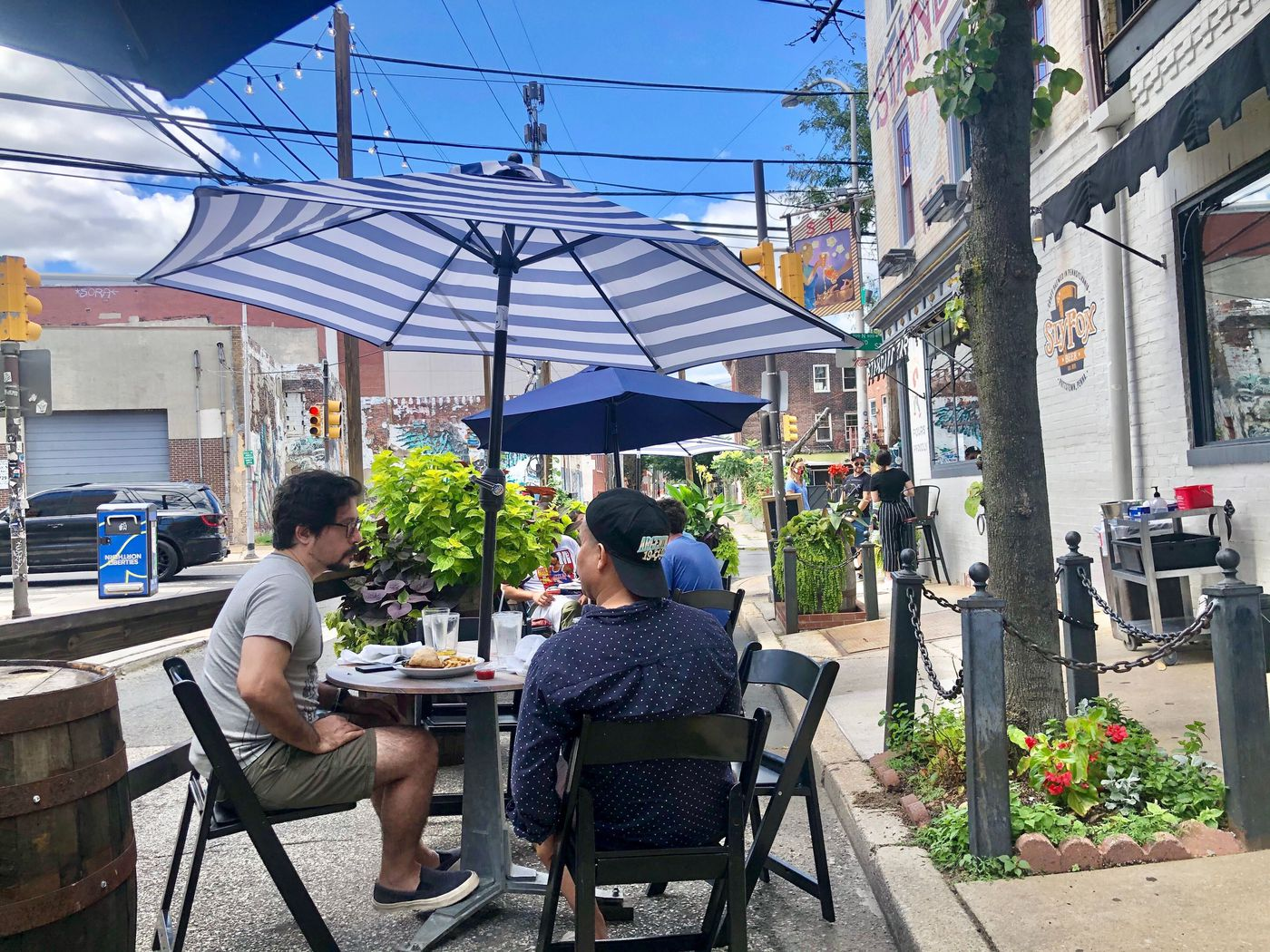 Diners enjoy a weekend brunch outdoors on the Poplar Street side of Standard Tap in Northern Liberties, where the tables are well spaced and landscaped with flowering plants.