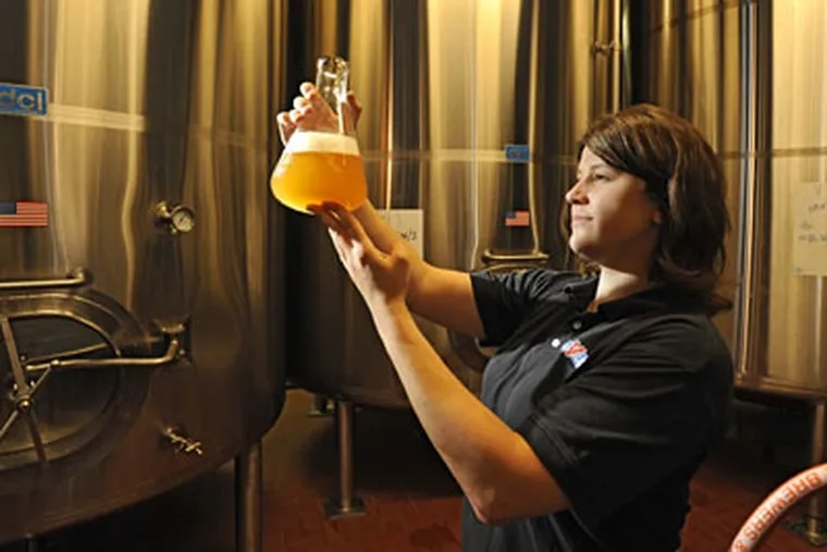 Whitney Thompson holds up a beaker of Prima Pilsner, inspecting its clarity during the brewing process at Victory Brewing Company in Downingtown. (CLEM MURAY / Staff Photographer)