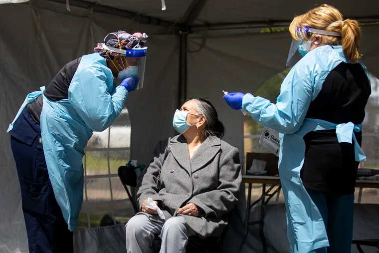 Tijuana Johnson, LPN at Cooper University Health Care, instructs a woman to reveal her nose to conduct the test for the coronavirus at a testing site in Dudley Grange Park in Camden on Tuesday.