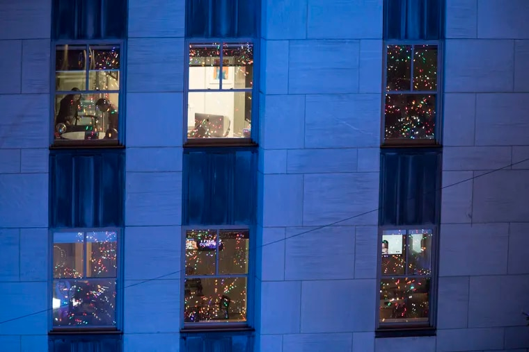 In this Nov. 28, 2018, file photo, people work in their office after the Rockefeller Center Christmas tree is lit during the 86th annual Rockefeller Center Christmas tree lighting ceremony in New York. Holiday staffing is one of a small business owner's biggest stressors. But giving gifts or bonuses is a way for employees to feel valued.  (AP Photo/Mary Altaffer, File)
