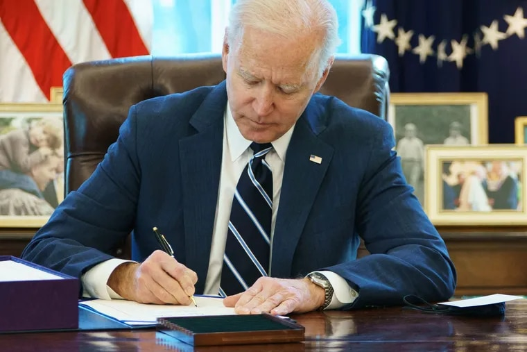 President Joe Biden signs the American Rescue Plan on March 11, 2021, in the Oval Office of the White House.