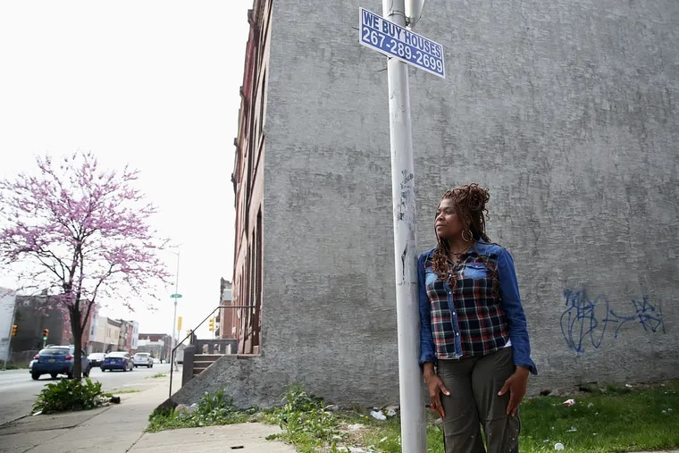 """Tonetta Graham, president of the Strawberry Mansion Community Development Corporation, under a """"We Buy Houses"""" sign in Philadelphia's Strawberry Mansion section. Her organization has been urging neighborhood homeowners to be wary of aggressive home purchasing efforts."""