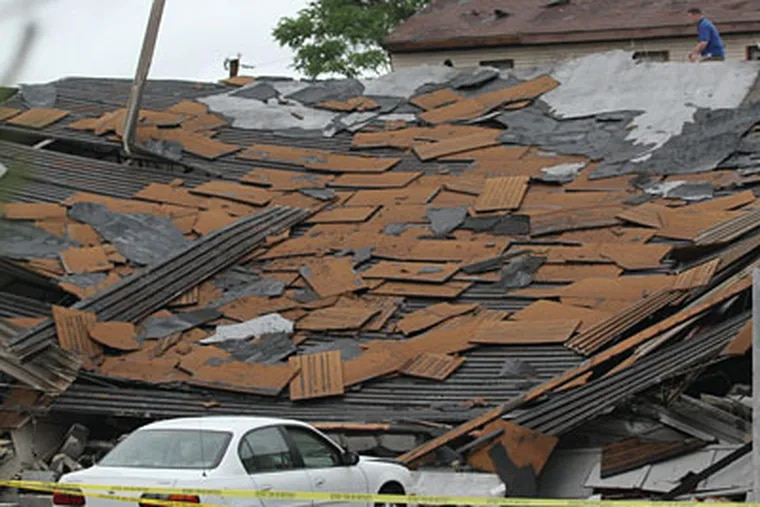 Frank Lubinsky Jr, of Union Roofing is on the collapse roof of R & R Car Repair at 9909 Northeast Ave., where a tornado was suppose to have touched down. One person was under it when it collapsed but was unharmed and crawled out right after the collapse. (Michael Bryant / Staff Photographer)