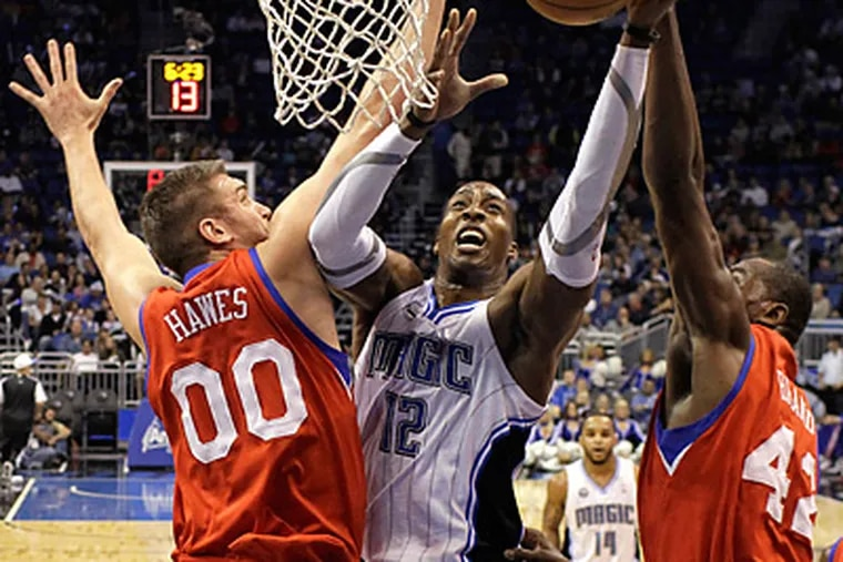 Orlando Magic center Dwight Howard tries to get a shot off between Spencer Hawes, left, and Elton Brand.  (AP Photo/John Raoux)