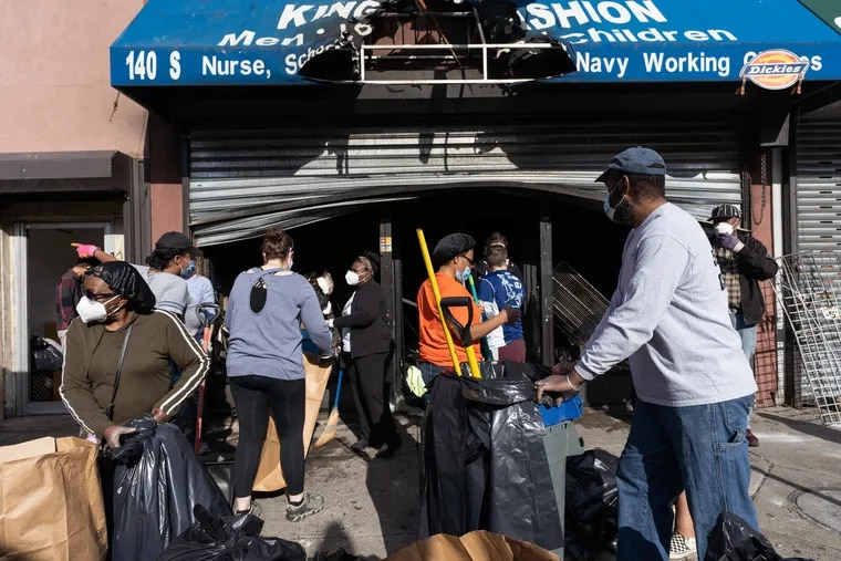 Community members clean up damage and vandalism at a store that was burned out on 52nd Street today in West Philadelphia, June 01, 2020.
