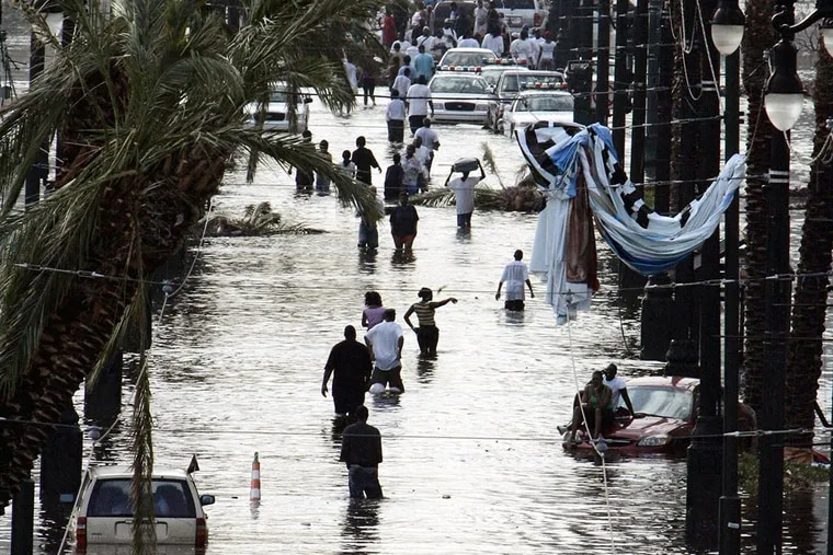 Residents walking through floodwaters on Canal Street in New Orleans in 2005 after Hurricane Katrina devastated the Louisiana and Mississippi coasts. BILL HABER / Associated Press, File