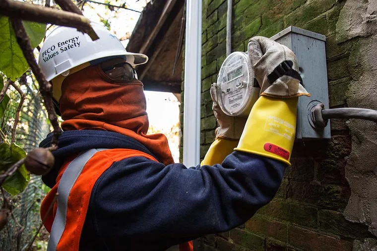 Peco technician Harry Christian, in protective gear, installs a smart meter. The five-year project is more than 99 percent done.