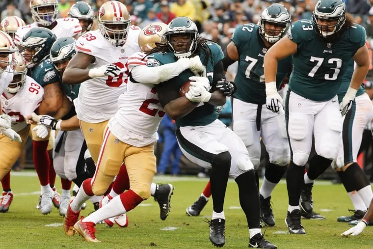 Eagles running back LeGarrette Blount, right, gets wrapped up by San Francisco 49ers cornerback Ahkello Witherspoon, left, last week.