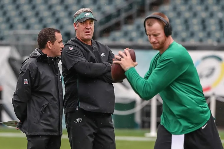 Former Eagles head coach Doug Pederson (center) and general manager Howie Roseman, and the man who ruined them both: Carson Wentz.