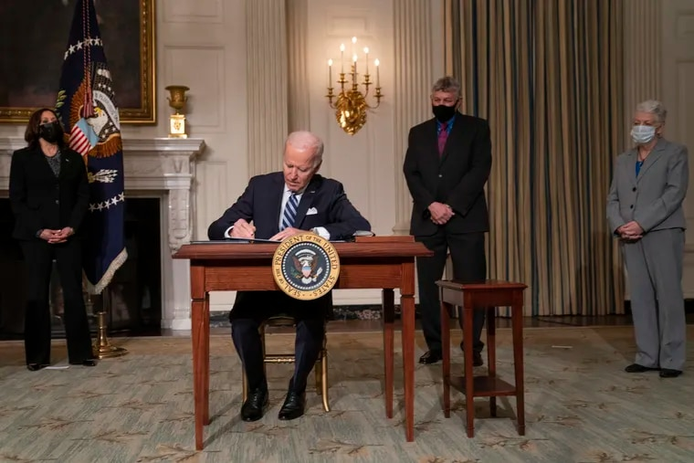 President Joe Biden signs a series of executive orders on climate change, in the State Dining Room of the White House on Jan. 27, 2021.  From left, Vice President Kamala Harris, Biden, White House science adviser Dr. Eric Lander, and National Climate Adviser Gina McCarthy.