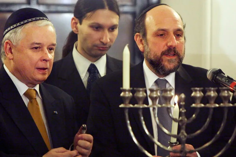 Poland's President Lech Kaczynski (left) stands with his country's chief rabbi, Michael Schudrich, at a Hanukkah celebration in Warsaw. Looking on is Israel's culture attache, Alon Simhayoff.