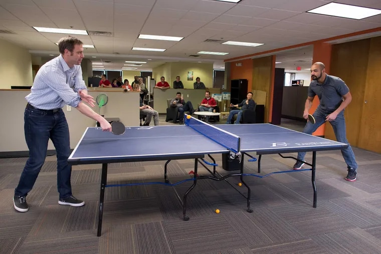 Brian Fenn (left) takes on Ryan Morris in a Friday afternoon game of ping-pong at Advanceon in Exton. Fenn, vice president of operations, admits he isn't the most skilled member of his tourney team.