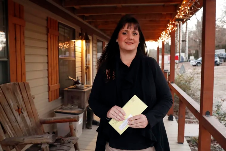 In this Thursday, Dec. 20, 2018 photo, Reagen Adair holds on to a RIP Medical Debt yellow envelope as she poses for a photo at her home in Murchison, Texas. The co-founders of RIP Medical Debt buy millions of dollars in past-due medical debt for pennies on the dollar. But instead of hounding people to pay, they send letters saying the debt is erased, no strings attached.  (AP Photo/Tony Gutierrez)