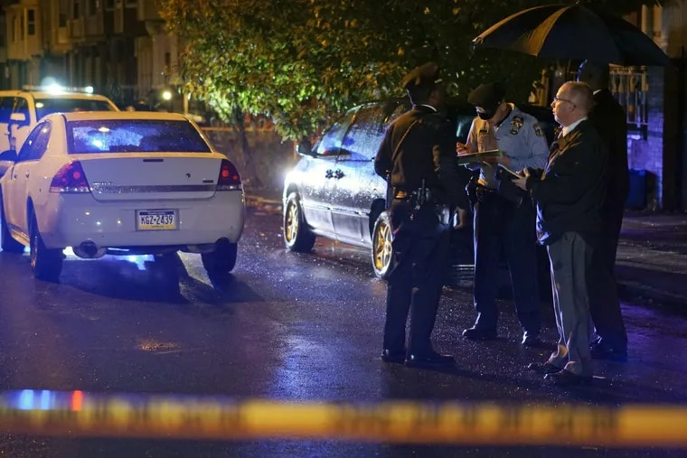 Homicide investigators gather on North 19th Street near West Somerset Street in North Philadelphia after a gunman opened fire early Sunday morning killing one teenager and injuring a 12-year-old.