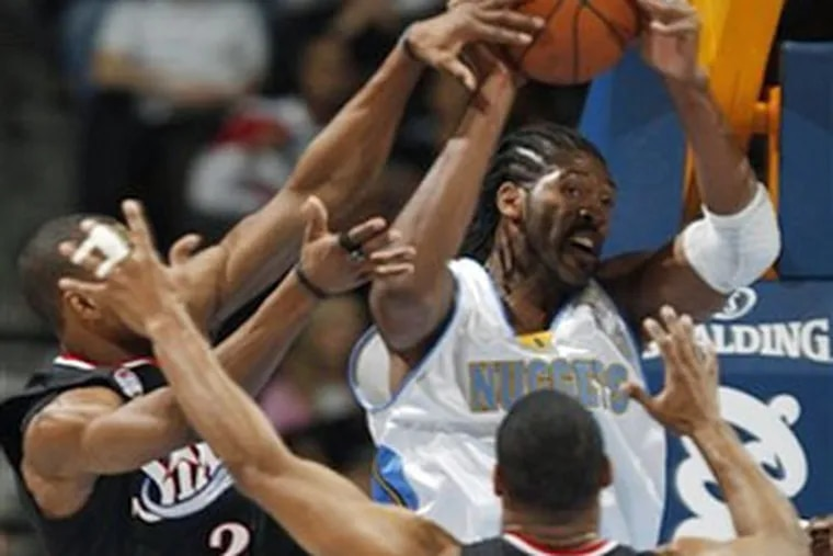 Denver Nuggets forward Nene Hilario, back right, of Brazil, looks to pass the ball after pulling down a rebound in front of 76ers forward Thaddeus Young, back left, and guard Willie Green in the first quarter Friday. The Sixers lost, 105-101. (AP Photo)