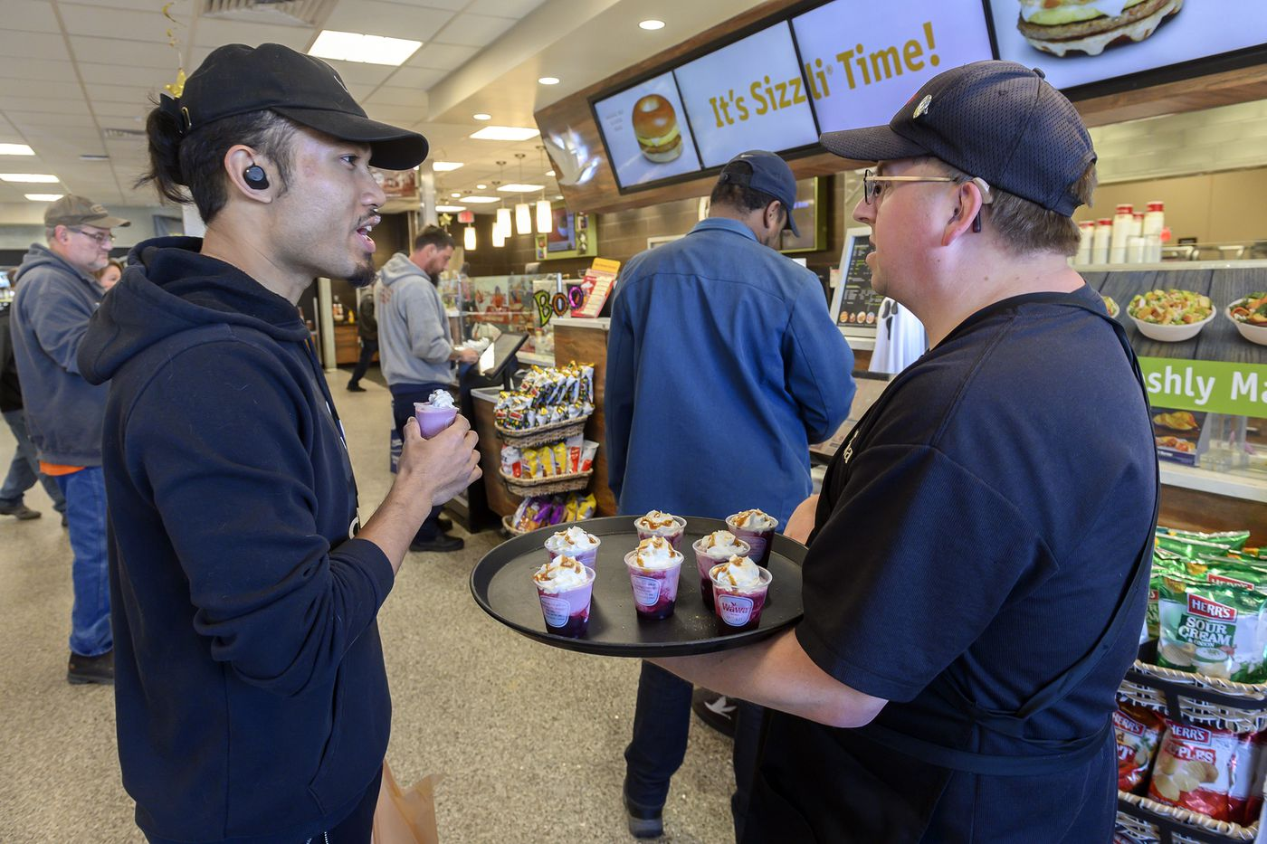 John Mitchell (right), a long-time Wawa employee, with customer Tony Kruth of South Philadelphia as he gives out samples of blender drinks.