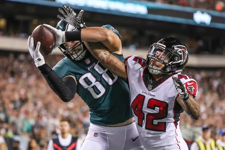 Eagles tight end Dallas Goedert, left, could not hold onto the pass in the end zone as Falcons LB Duke Riley  broke it up in  September 2018.