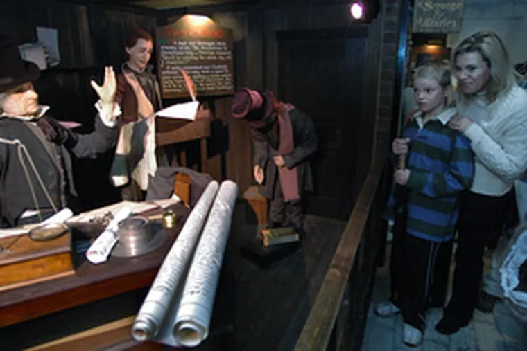 """Before an animatronic scene from Dickens' """"A Christmas Carol"""" at Macy's are visitors Billy Murphy, 10, of Malvern, and his mother, Patti. The display was created in 1984 for Strawbridge & Clothier."""