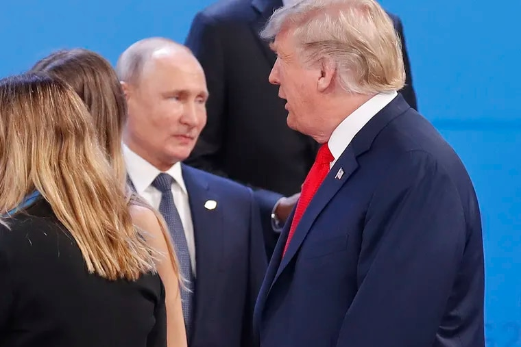 Russia's President Vladimir Putin, left, watches President Donald Trump, right, walk past him as they gather for the group photo at the start of the G20 summit in Buenos Aires, Argentina, Friday, Nov. 30, 2018. Leaders from the Group of 20 industrialized nations are meeting in Buenos Aires for two days starting today.(AP Photo/Pablo Martinez Monsivais)