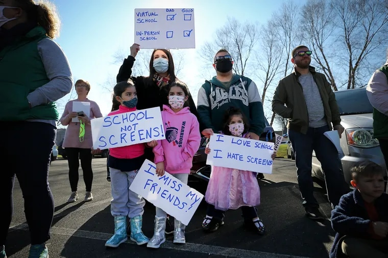 Barbara Roque (top left) holds up a sign during Sunday's rallyin Horsham. She was with her children (from left to right) Elaina, Emily and, Erica, and her husband David.
