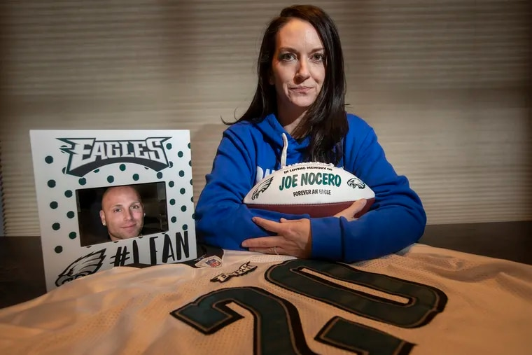 Melissa Nocero, in her Jamison home, with the ball the Eagles organization gave her family with her husband Joe Nocero's name painted on it; her husband's favorite player's jersey, Brian Dawkins' No. 20; and his photo in a frame that a friend gave her after his death.