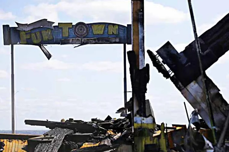 The sign for Funtown Pier stands above charred rubble in Seaside Park, N.J., Tuesday, Sept. 17, 2013, after a fire last Thursday that started near a frozen custard stand in Seaside Park,  quickly spread north into neighboring Seaside Heights. More than 50 businesses in the two towns were destroyed. The massive boardwalk fire in New Jersey began accidentally, the result of an electrical problem, an official briefed on the investigation said Tuesday. (AP Photo/Mel Evans)