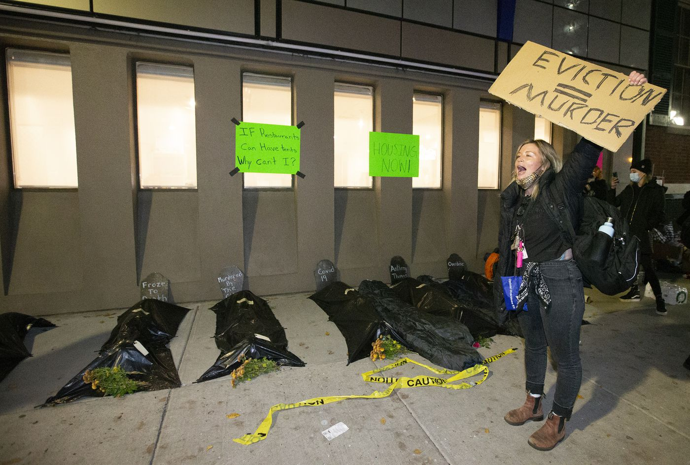 Veronica Carden of Club Sandwich Philly, stands outside the Holiday Inn with fake body bags on the sidewalk as advocates for the homeless created an encampment on Dec. 10.