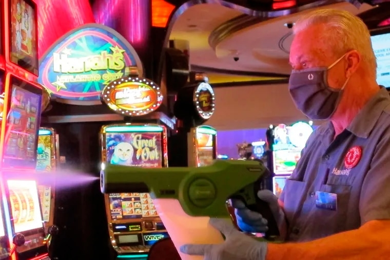 In this July 1 photo, Steven Ford, a worker at Harrah's casino in Atlantic City, N.J., sprays slot machines with disinfectant as the casino prepared to reopen after 3 1/2 months of being shut down because of the coronavirus.