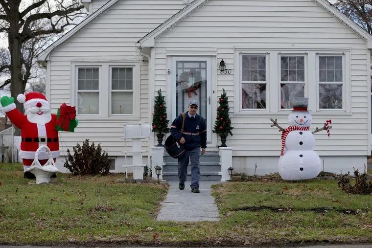 Postal carrier Tom Tryon visits a home along Oak Avenue in Croydon, PA on December 4, 2018.