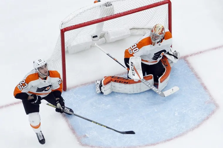 Flyers' Brandon Manning (23) keeps his eye on the puck along side goalie Michal Neuvirth during the team's 2-0 win over the Blues.