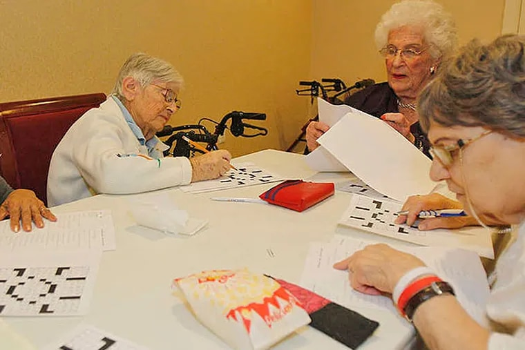 Bernice Gordon (second from right) leads a class on working crossword puzzles at her apartment, joined by her friends (from left) Julie Patillo, Ann Frank, and Fran D'Urbano. AKIRA SUWA /Staff Photographer