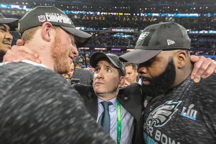 Eagle vice president Howey Roseman hugs Carson Wentz, left, adn Jason Peters, right, on the field after the Eagles defeated the New England Patriots in Super Bowl LII in Minneapolis MN on Febuary, 2018. MICHAEL BRYANT/ Staff Photographer
