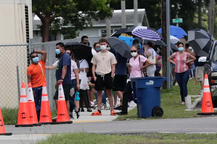 People wait in line outside of a COVID-19 testing site during the coronavirus pandemic, Thursday, July 16, 2020, in Opa-locka, Fla. (AP Photo/Lynne Sladky)