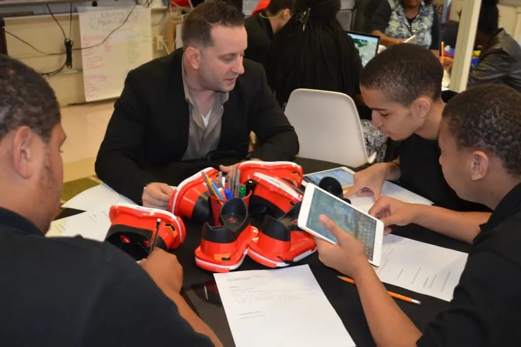 Camden teacher Thomas Levy has raised thousands of dollars worth of classroom supplies and equipment for his students at Woodrow Wilson High School through Donors Choose, an online crowd-funding tool. Here, Levy works with students using technology paid for by donors.