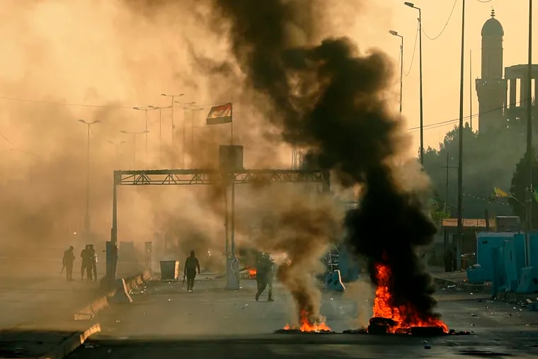 Iraqi security forces fire tear gas to disperse anti-government protesters who set fires and close a street during a demonstration in Baghdad, Iraq, Saturday, Oct. 5, 2019. The spontaneous protests were sparked by endemic corruption and lack of jobs.