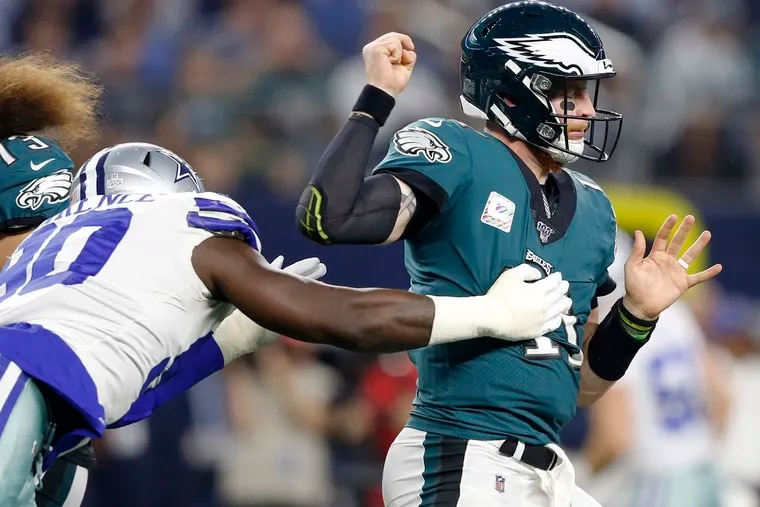 Dallas Cowboys defensive end Demarcus Lawrence (90) strips the ball from Philadelphia Eagles quarterback Carson Wentz (11) during the first half on Sunday, Oct. 20, 2019 at AT&T Stadium in Arlington, Texas. (Vernon Bryant/The Dallas Morning News/TNS)