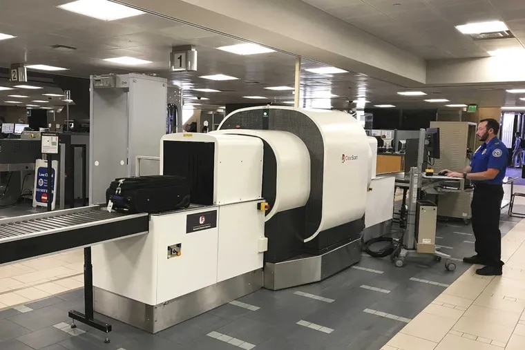 A Transportation Security Administration officer operates a baggage scanner.