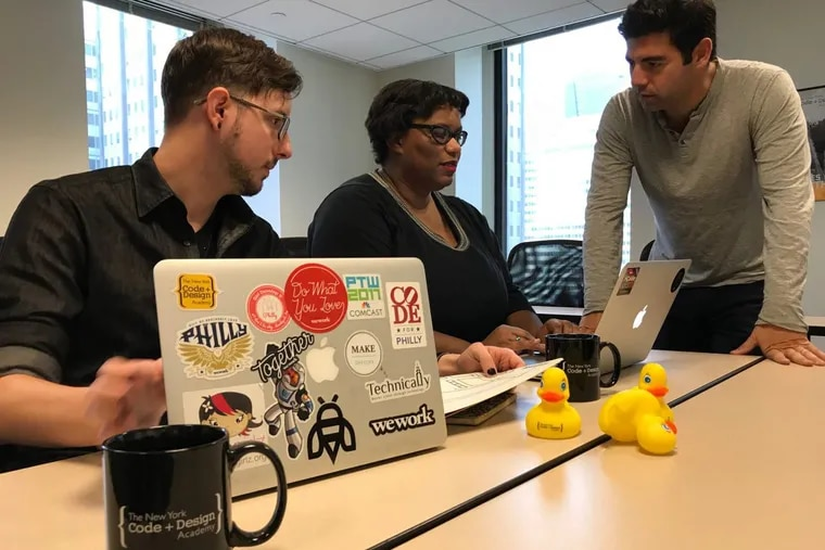 New York Code + Design Academy founder/CEO Jeremy Snepar (standing) confers with Philly students Dallas Peterson and Angel Young at the school's Cherry Street campus.
