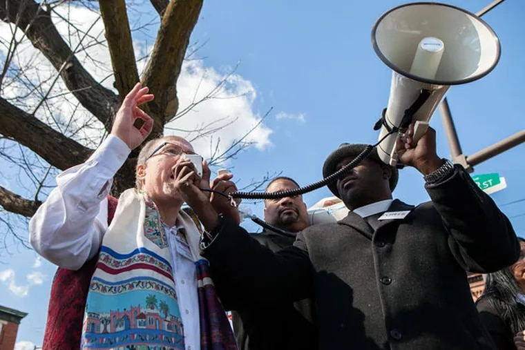 The Rev. Mark Tyler, pastor of Mother Bethel AME Church, holds the megaphone for Rabbi Shawn Zevit of Mishkan Shalom while he addresses the crowd Saturday, April 4, 2015. (CHRIS FASCENELLI/Staff Photographer)