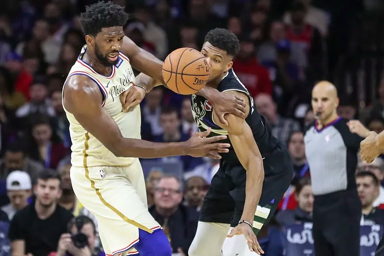 Giannis Antetokounmpo is called for a foul against Joel Embiid in the second quarter of a game at the Wells Fargo Center in South Philadelphia on Wednesday, Dec. 25, 2019. Sixers won, 121-109.