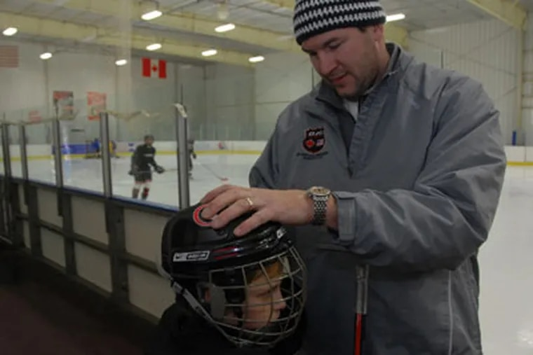 Keith Primeau adjusts the helmet of  Wyatt  Dugan of Haddonfield, NJ, one of the players on the team he coaches at the Flyers Skate Zone in Pennsauken.  (Photo / Curt Hudson)