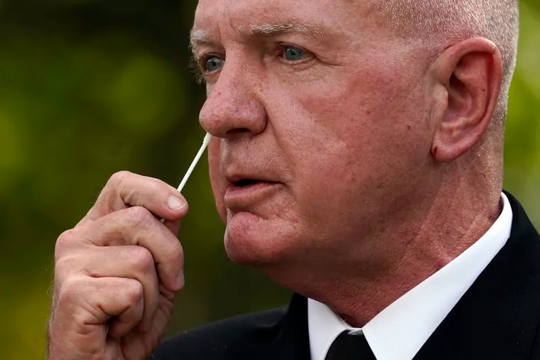 Adm. Brett Giroir, assistant secretary of Health and Human Services, swabs his nose as he demonstrates a new fast result COVID-19 antigen test during an event with President Donald Trump at the White House on Monday. (AP Photo/Evan Vucci)