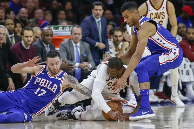 Cavaliers guard Dwyane Wade goes after a loose ball with Sixers guard JJ Redick (left) and guard Timothe Luwawu-Cabarrot (right) during the first quarter Monday.
