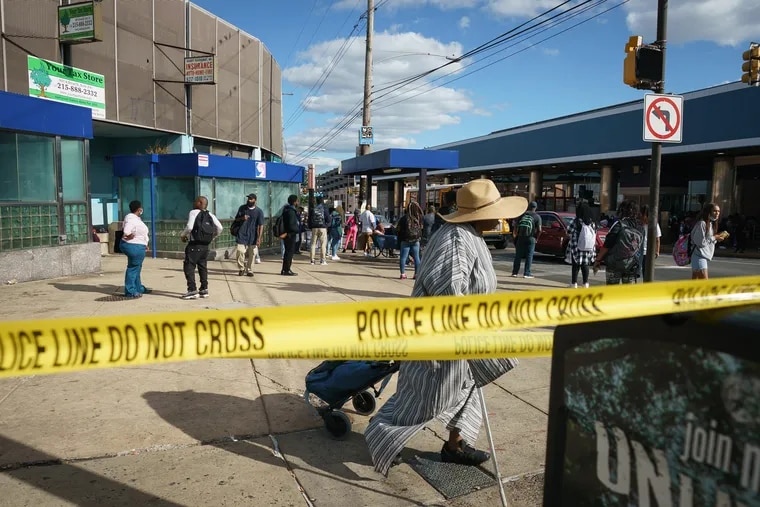 Commuters walk past crime scene tape at Broad Street and Olney Avenue, one block away a shooting that left one person dead and five wounded on Monday.