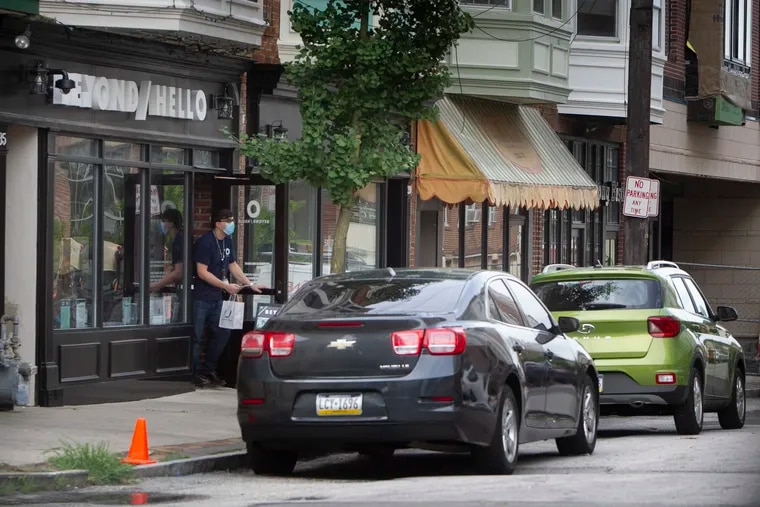 Curb service for patron of Beyond / Hello a cannabis dispensary at 35 Cricket Avenue in Ardmore, PA on Thursday, August 13, 2020. Employee delivers to little green car.