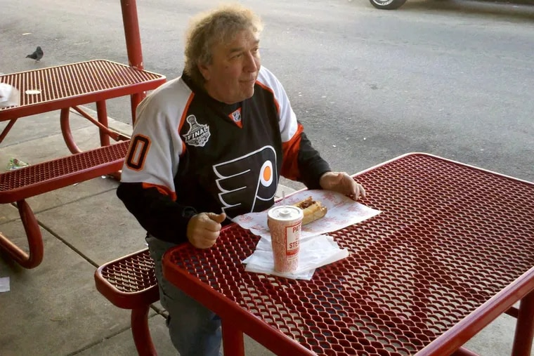 Richard Lussi, seen here eating at Pat's King of Steaks, asked to be buried wit his favorite sandwich when he expired.