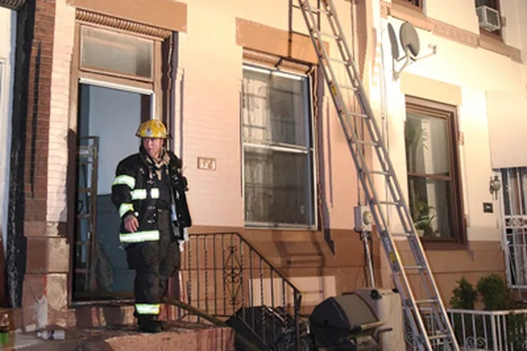 A 10-year-old boy is still in critical condition after being rescued from his burning Strawberry Mansion row home, at 821 N. 27th Street, at about 10 p.m. Monday. (Steven M. Falk / Staff Photographer)