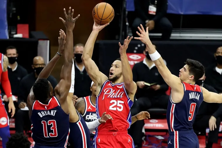 Ben Simmons, center, of the SIxers goes up for a shot between Thomas Bryant, left,  and Deni Avdija of the Wizards during the first half of Wednesday's 113-107 win.